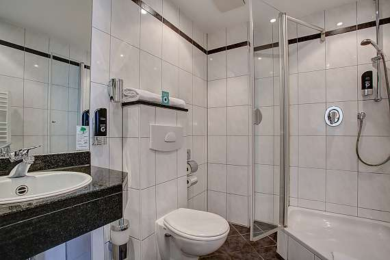 Large bathroom with hairdryer, personal care products and shower